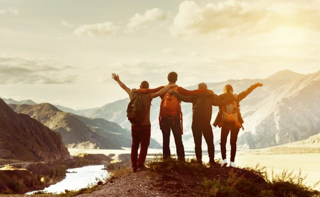 Group of friends overlooking cliffside into mountain range